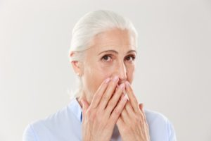 older woman embarrassed needs to visit prosthodontist in la mesa