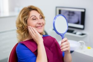 person sitting in the dental office looking at their new dental implants in San Diego in a small mirror